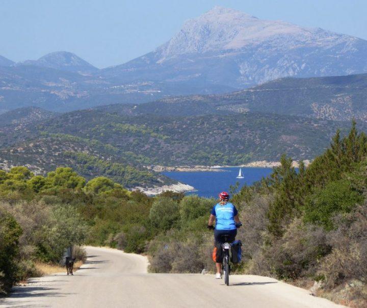 Cyklist på vej ned ad bakke i smukt landskab på øen Poros i Kykladerne
