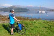 Cyklist med udsigt over det spejlblank vand med en skonnert for anker