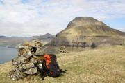 Udsigt til færøske fjelde med varde og rygsæk i forgrunden