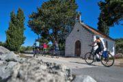 Cyklister passerer et lille kapel på øen Solta