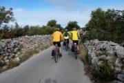 Cyklister på smal asfaltvej mellem stenmure